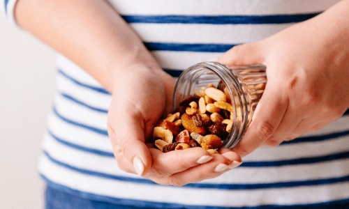 Person pouring out nuts in hand