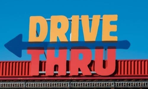 Yellow and red drive thru sign with blue arrow pointing left