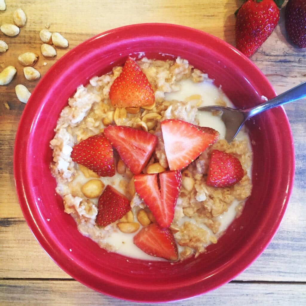 Oatmeal with strawberries and peanuts in a red bowl on a wooden table.