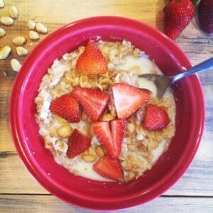 Kidney-friendly oatmeal with strawberries and peanuts in a red bowl on a wooden table.